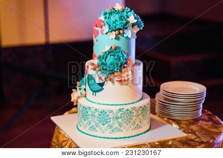 Large Wedding Cake With Three Tiers Of White Blue Glaze Decorated With Flowers And Hearts On The Tab