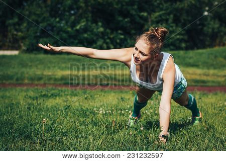 Female Athlete Does Sport Exercises In The Stadium In A Summer Day