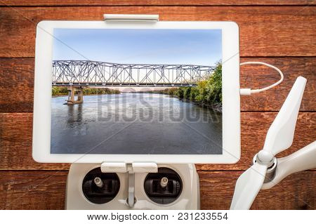 Missouri River bridge and I-70 highway near Rocheport, MO (Taylor's Landing) - reviewing an aerial image on a digital tbalet mounted on a drone radio controller