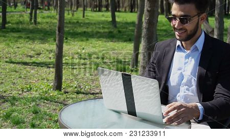 Author Uses Laptop And Clicking Buttons On Keyboard. Smiling Man Has Short Dark Hair, Beard And Dimp