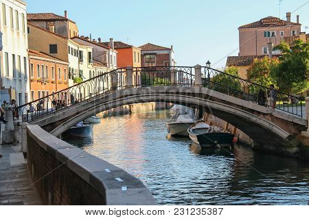 Venice, Italy - August 13, 2016: Tourists Walking On Famous Water Streets Of Historic City Center