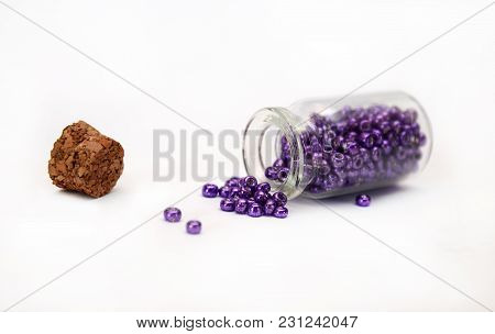 Lilac Beads In Bottle With Cork On White Background