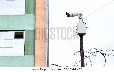 Camera Video Surveillance On The Building Background Mounted On A Brick Wall, Fenced With Barbed Wir
