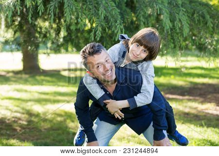 Portrait of father with his son having fun in summer park. Piggyback. Family fun. Happy boy playing with dad summer nature outdoor. Parenting. Two generations.