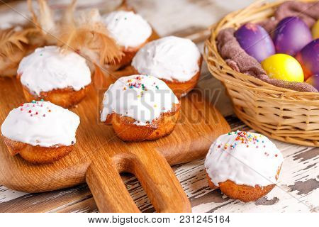 Fresh Pastry With Sugar Icing On A Wooden Board And Basket With Painted Eggs.