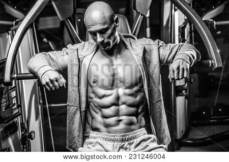 Handsome Young Muscular Caucasian Man Of Model Appearance Workout Training Arms In Gym Gaining Weigh