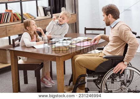 Father On Wheelchair Helping Kids With Education At Home