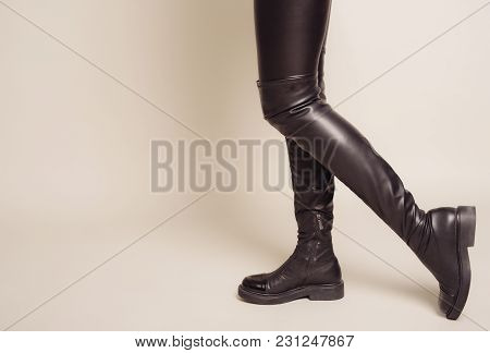 Slim Women's Legs In Black Leather Pants And Stylish High Boots Stands Sideways