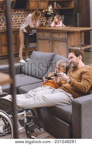Selective Focus Of Happy Disabled Father With Legs On Wheelchair And Cute Little Son Playing With Jo