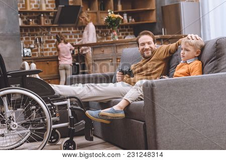 Happy Disabled Father With Legs On Wheelchair And Cute Little Son Playing With Joysticks Together At