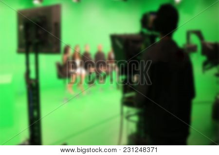 Blur Image A Television Presenter In A Tv Camera In Studio A Green Screen.