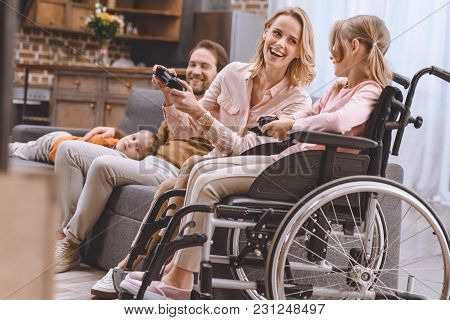 Family With Disabled Child In Wheelchair Playing With Joysticks Together At Home