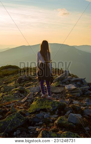 Teenage Girl Stands On The Top Among Stones During Sunset, Admires The Panorama Of The Mountains In
