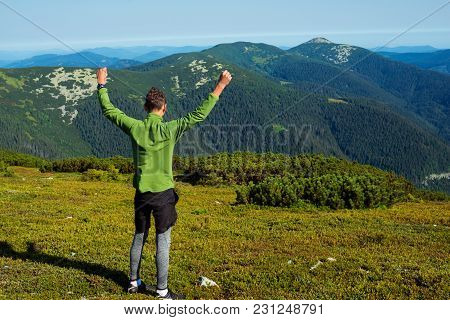 Joyful Hiker, Young Guy Stands With Open Arms In The Mountains At Sunny Morning, Admires The Amazing