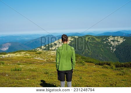 Hiker, Young Guy Stands In The Mountains At Sunny Morning, Admires The Amazing View Of The Green Mou