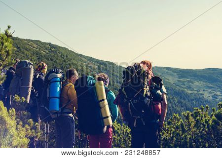 Hikers, Company Of Friends Are Standing On A Rocky Path, Admiring The Panorama Of Mountains Covered