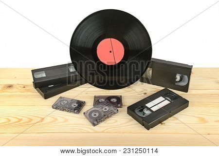 Composition of vinyl disc, audiocassettes and videocassettes on wooden table. Copy space
