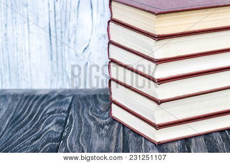 A Stack Of Red Books On A Wooden Table. Concept Of Reading Habits