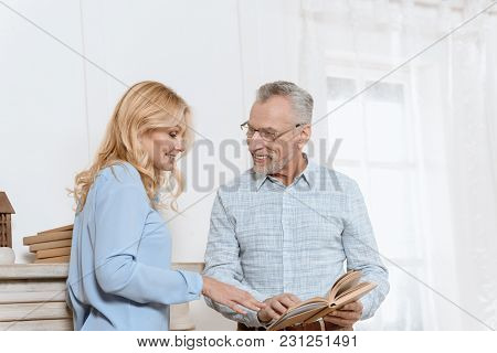 Mature Woman And Man Reading Book Together By Window In Light Room
