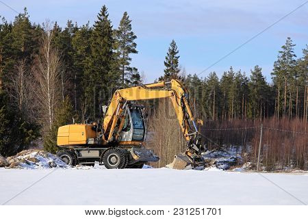 Yellow Mid-size Hydraulic Excavator At Rural Construction Site With Forest On The Background On A Su