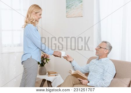 Mature Man Reading Book While Woman Serves Him Tea In Light Room