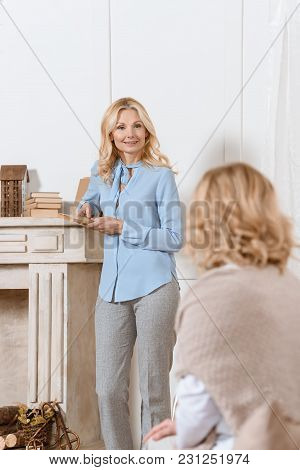 Adult Woman Reading Book And Discussing It With Her Friend In Light Room