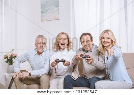 Middle Aged Men And Women Sitting On Sofa And Playing Game Console Using Joysticks