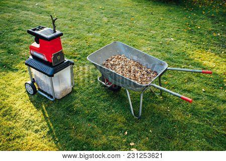garden chipper, electric shredder (mulcher) with wheelbarrow full of wooden mulch, green grass background