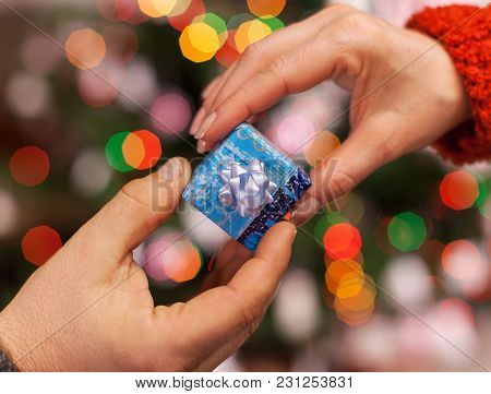 Hands Giving And Receiving Small Gift Package On Colorful Blurry Lights Background - Christmas  And