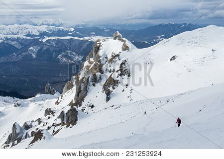 Lonely Hiker Descending Snowy Mountain Slope - More Snow Covered Peaks In The Background