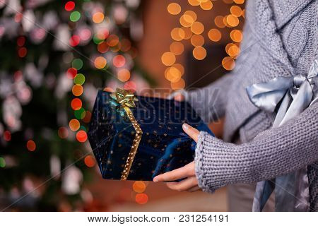 Young Girl Hands Offering Beautiful Wrapped Christmas Present - Closeup With Colorful Lights Backgro