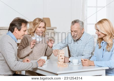 Happy Friends Sitting At Table With Tea And Playing Tower Game