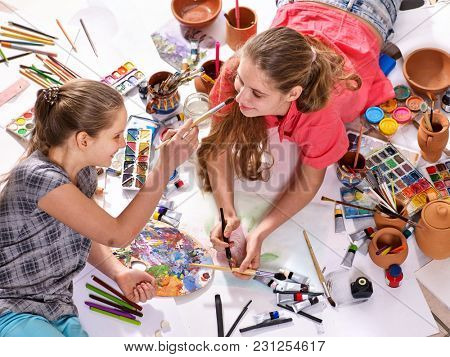 Authentic artist children girl paints with set palette watercolor paints palette and brush in morning sunlight. Painting in studio on floor. Good hobby for children.