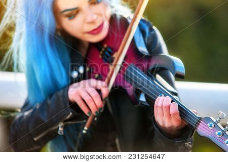 Woman perform music on violin in park outdoor. Girl with blue hairstyle performing jazz on city street. Sun flare of spring outside blur background. People make living by concerts.