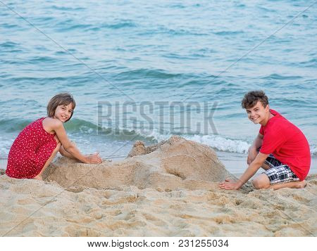 Happy Girl And Boy Playing On Sea Shore At Sandy Beach During Summer Holiday. Cute Children - Brothe