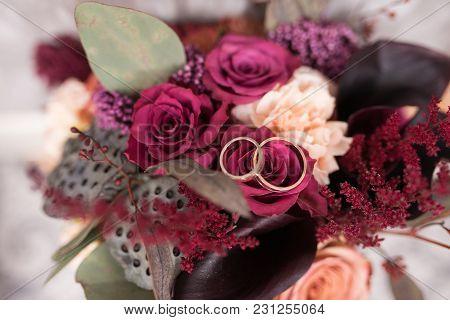 Golden Wedding Rings Lie In A Bud Of Pink Rose. Wedding Rings Lie On A Flower Bud