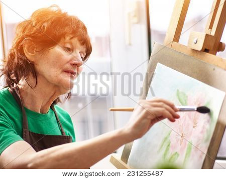 Artist painting easel in studio. Authentic senior woman has small home own business paints with brush in morning spring sunlight on window work place background. Workshop of professional artist.