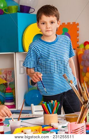 Small student boy painting in art school class. Child drawing paints on table. Boy in children's club. Craft drawing education develops creative abilities of children. Student selects paint brushes.