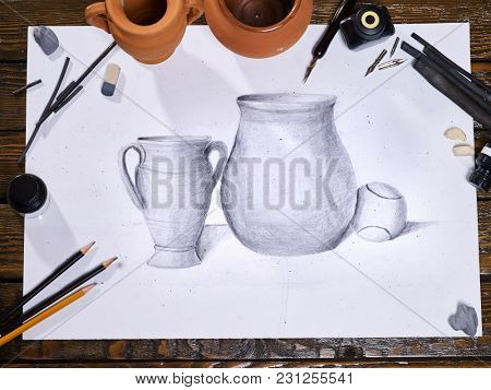 Drawing picture on table in art class school. Group of brush in clay jar on wooden table. Flowers as symbol of spring discounts. Training art graphics courses by nib pen. Drawing from nature to speed.