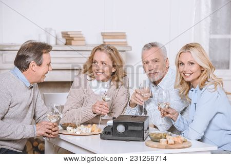 Friends Sitting At Table With Food And Projector In Room Interiorn