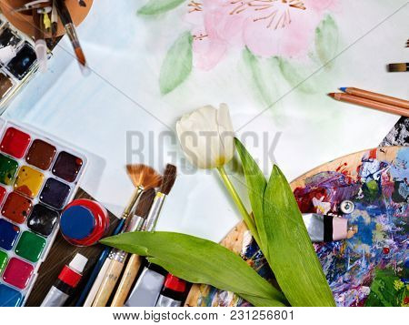 Authentic paint brushes still life in art class school. Group of brush in clay jar. Bouquet of tulip flowers as symbol of spring discounts. Copy space for text. Spring discounts. Drawing from nature.