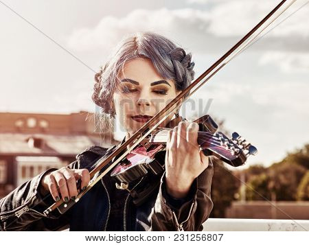 Woman perform music on violin in park outdoor. Girl with blue hairstyle performing jazz on city street. Spring outside blur background. Warm-glow toning of spring photo.
