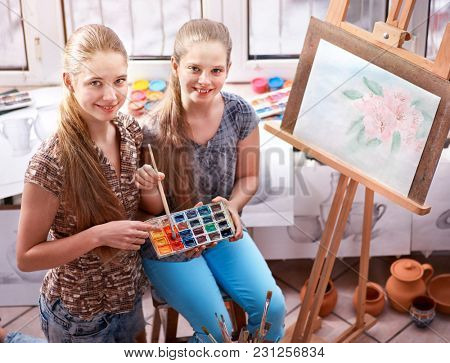 Artist painting easel in studio. Authentic children girl paints with set palette watercolor paints palette in morning sunlight . Top view school indoor interior crafts. Sisters working together.