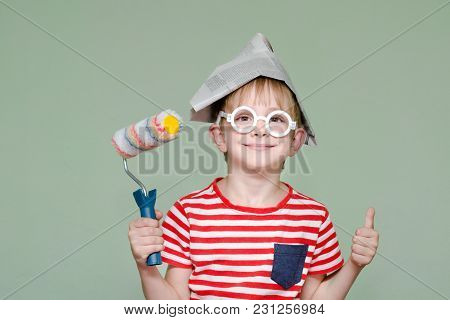 Boy In A Paper Hat And Glasses Shows The Cool. Portrait. Roller For Painting