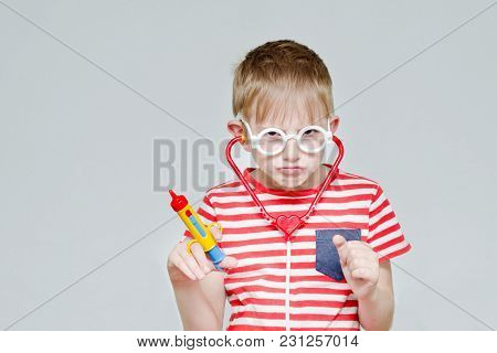 Funny Boy Playing Doctor. Toy Syringe, Glasses And Phonendoscope. Portrait