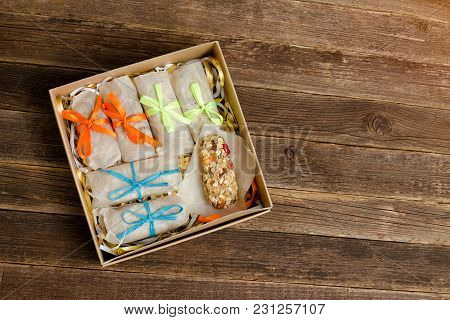 Boxes With Bars. One Without A Wrapper. Wooden Table
