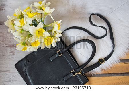 Black Hahdbag And Bouquet Of Daffodils On White Fur. Fashionable Concept