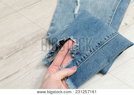 Ragged Jeans In Female Hand. Detail. Close Up