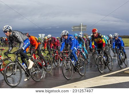 Cernay-la-ville, France - March 5, 2017: The Peloton Taking A Bend On A Wet Road During The First St