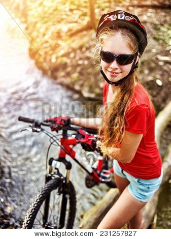 Cycling teen with ladies bikes in summer park. Woman road bike for running on nature. Teenager girl in helmet bicycle fording throught water. School trip. Sun flare background illumination.